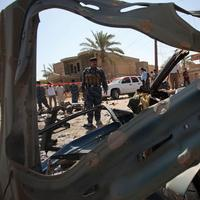 Iraqi security forces inspect the site of a suicide car bomber plowed his vehicle into a checkpoint outside a police building just outside the holy city of Najaf, Iraq. (AP)