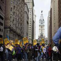 Members of Service Employees International Union march from the encampment at City Hall, center, Tuesday. (AP)