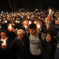 People gather in front of the Old Main building for a candlelight vigil in support of child abuse victims on the Penn State campus on Friday, in State College, PA.