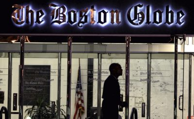 A security guard walks past the entrance of  the Boston Globe building in Dorchester on July 20, 2009. (Charles Krupa/AP)