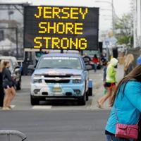 Angelina Zuzuro, 16, of Denville, takes photos near a sign in Seaside Heights, N.J., Saturday, May 18, 2013. (Mel Evans/AP)