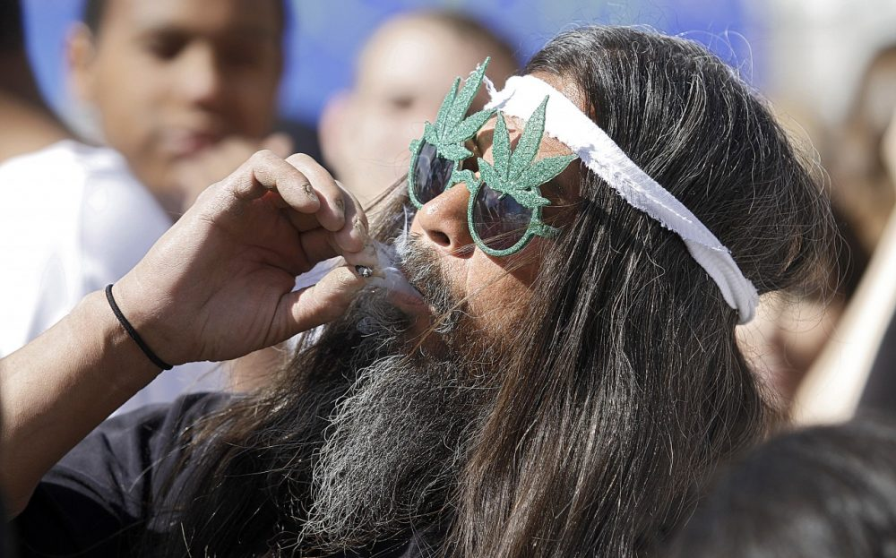 Fast Eddy Aki'a of Hawaii smokes a joint as thousands gathered to celebrate the state's medicinal marijuana laws and collectively light up at 4:20 p.m. in Civic Center Park April 20, 2012 in Denver, Colorado. (Marc Piscotty/Getty Images)