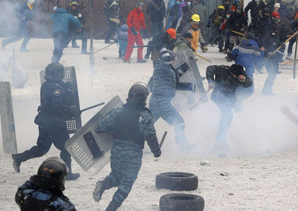 A police officer beats a protester during clashes in central Kiev, Ukraine, Wednesday. (Sergei Grits/AP)
