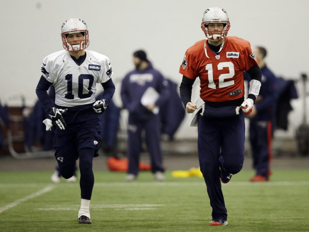 New England Patriots quarterback Tom Brady (12) and wide receiver Austin Collie (10) run during a stretching session before NFL football practice at the team's facility in Foxborough, Mass., Tuesday, Jan. 7, 2014. The Patriots are scheduled to host the Indianapolis Colts in an NFL football divisional playoff game on Saturday, Jan. 11. (AP)