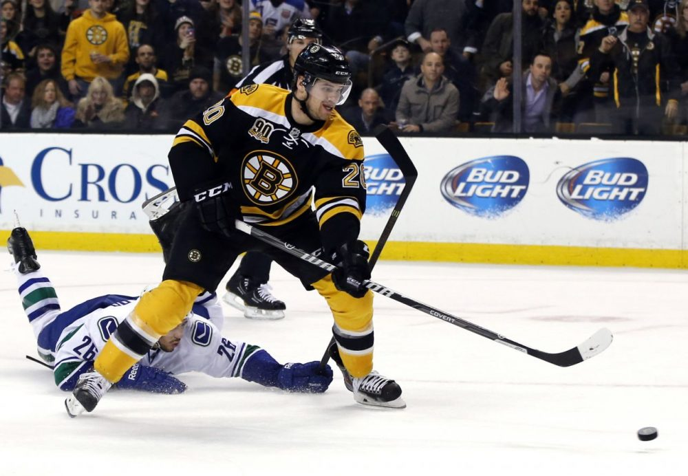Boston Bruins left wing Daniel Paille (20) shoots and scores on a breakaway as Vancouver Canucks defenseman Frank Corrado (26) tries to stop him during the second period. (Elise Amendola/AP)