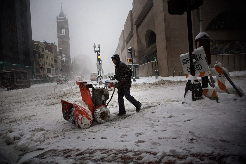 A snow plow operator works in front of Boston's Lenox Hotel Wednesday morning. (Jesse Costa/WBUR)