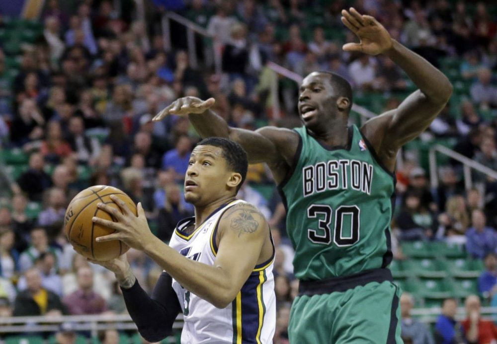 Utah Jazz's Trey Burke, left, goes to the basket as Boston Celtics' Brandon Bass (30).(AP/Rick Bowmer)