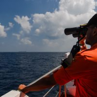 An Indonesian National Search and Rescue Agency personnel scans the seas aboard a boat on patrol in the Malacca Strait off Aceh province located in the area of northern Sumatra island on March 12, 2014, during the continued search for the missing Malaysia Airlines flight MH370. (STR/AFP/Getty Images)