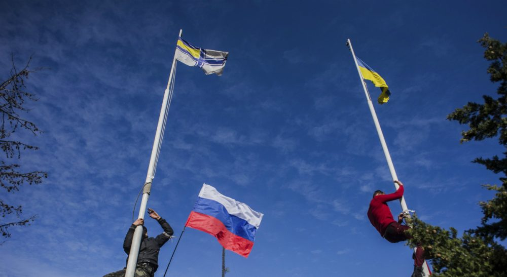 Members of the Crimean pro-Russian self-defense forces climb up to take down a Ukrainian flag, right, and a Ukrainian navy flag, left, at the Ukrainian navy headquarters in Sevastopol, Crimea, Wednesday, March 19, 2014. In center is a Russian flag. (Andrew Lubimov/AP)