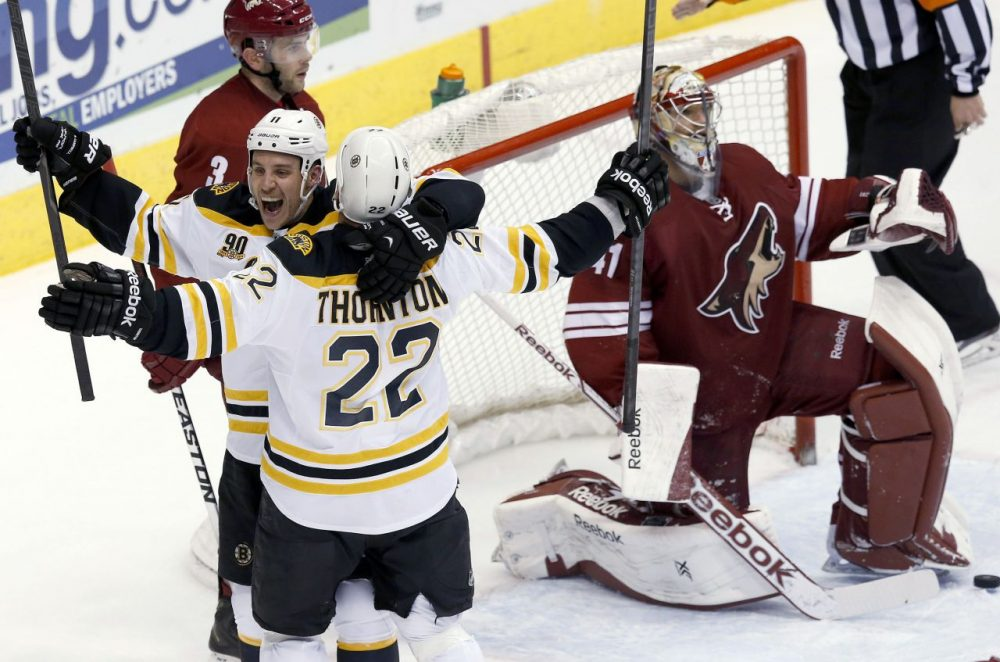 Boston Bruins' Shawn Thornton (22) celebrates his goal against Phoenix Coyotes' Mike Smith, right, with teammate Gregory Campbell (11) as Coyotes' Keith Yandle (3) skates past during the third period of an NHL hockey game Saturday, March 22, 2014, in Glendale, Ariz. The Bruins defeated the Coyotes 4-2. (Ross D. Franklin/AP)
