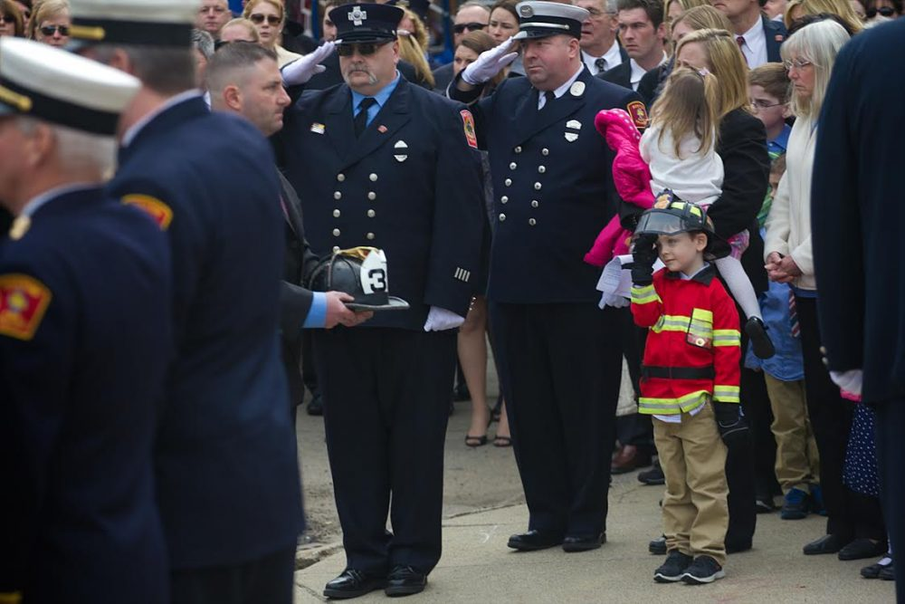 Robert Malone, the nephew of Lt. Edward Walsh, salutes as his uncle's fire helmet is carried into St. Patrick's Church in Watertown Wednesday morning.  (Jesse Costa/WBUR)