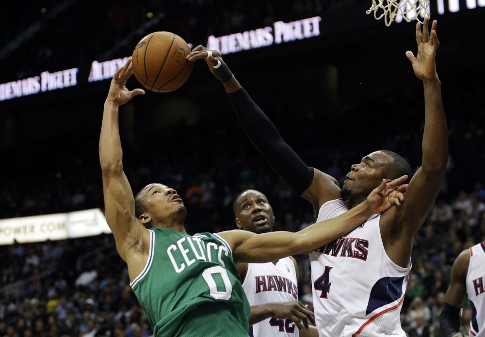 Atlanta Hawks' Paul Millsap, right, reaches for a loose ball against Boston Celtics' Avery Bradley in the fourth quarter. (David Goldman/AP)