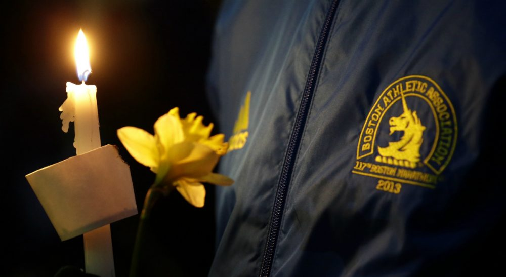 The first anniversary of the marathon attack has Anita Diamant thinking about the families of those who lost their lives. This photo was taken at a vigil for the victims of the Boston Marathon explosions, Tuesday April 16, 2013. (Julio Cortez/AP)