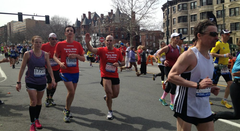 Peter Sagal runs next to William Greer around Mile 24 of the 2013 Boston Marathon. This picture was taken roughly 20 minutes before the bombs went off. (Linda McIntosh/Courtesy)