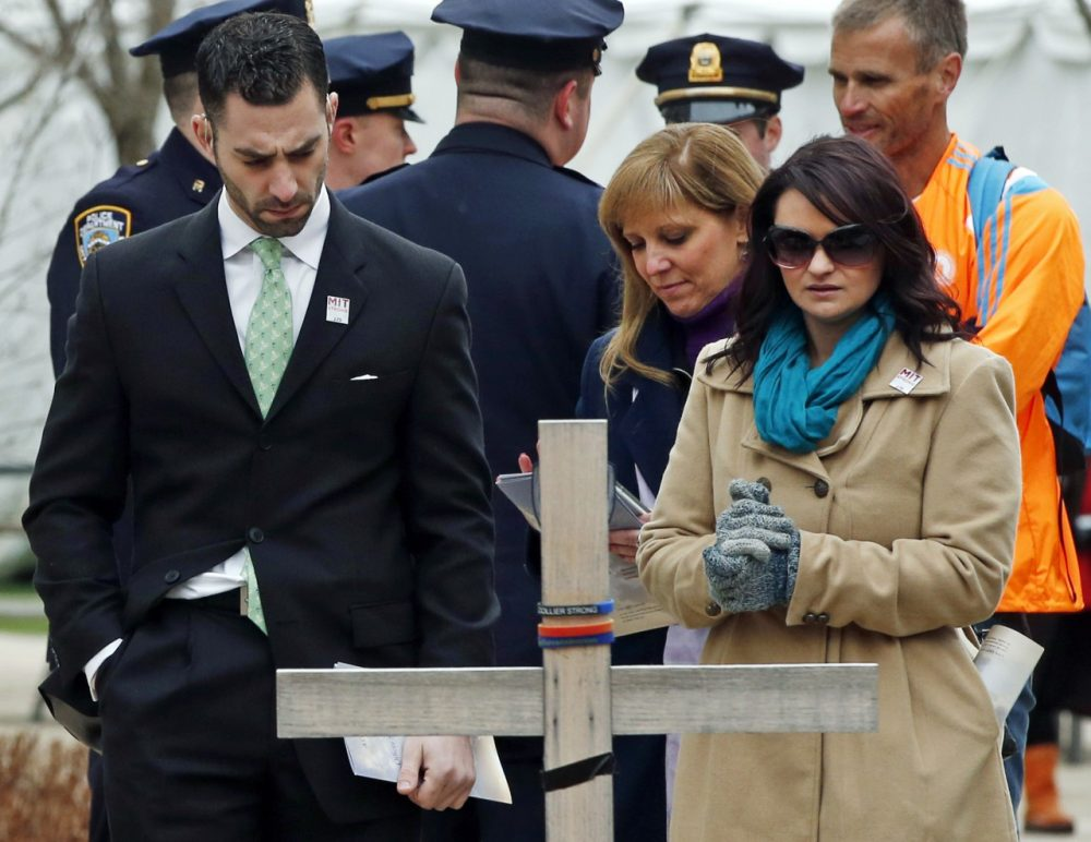 Police officers, friends and family members pause by a memorial cross and stone after attending a one-year remembrance ceremony for Massachusetts Institute of Technology Officer Sean Collier on campus in Cambridge, Mass., Friday, April 18, 2014. Authorities say Collier was slain by the suspects of the 2013 Boston Marathon bombing. (AP)