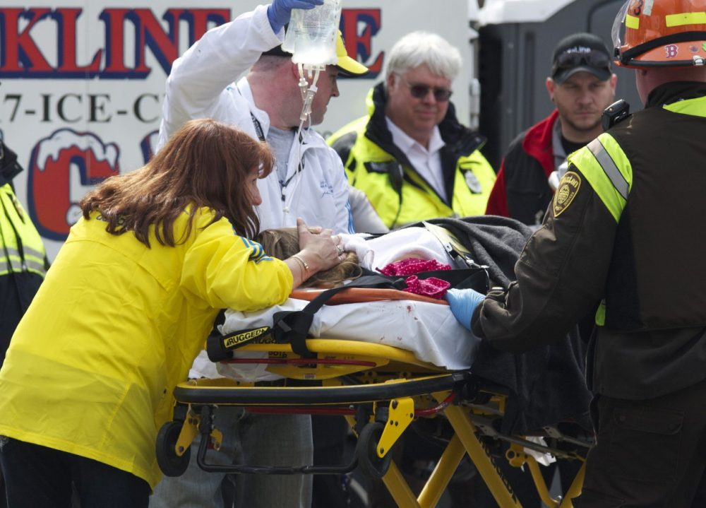 Alicia Shambo, in the yellow jacket, comforts Victoria McGrath, seriously injured in the bombing of the Boston Marathon,  as medics prepare to put McGrath into an ambulance Monday, April 15, 2013. (Jeremy Pavia/AP)