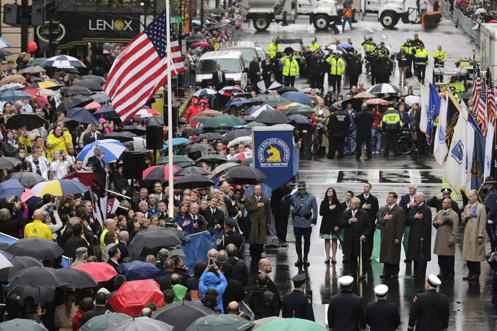Survivors, officials, first responders and guests pause as the flag is raised at the finish line during a tribute in honor of the one year anniversary of the Boston Marathon bombings, Tuesday, April 15, 2014 in Boston. (AP)