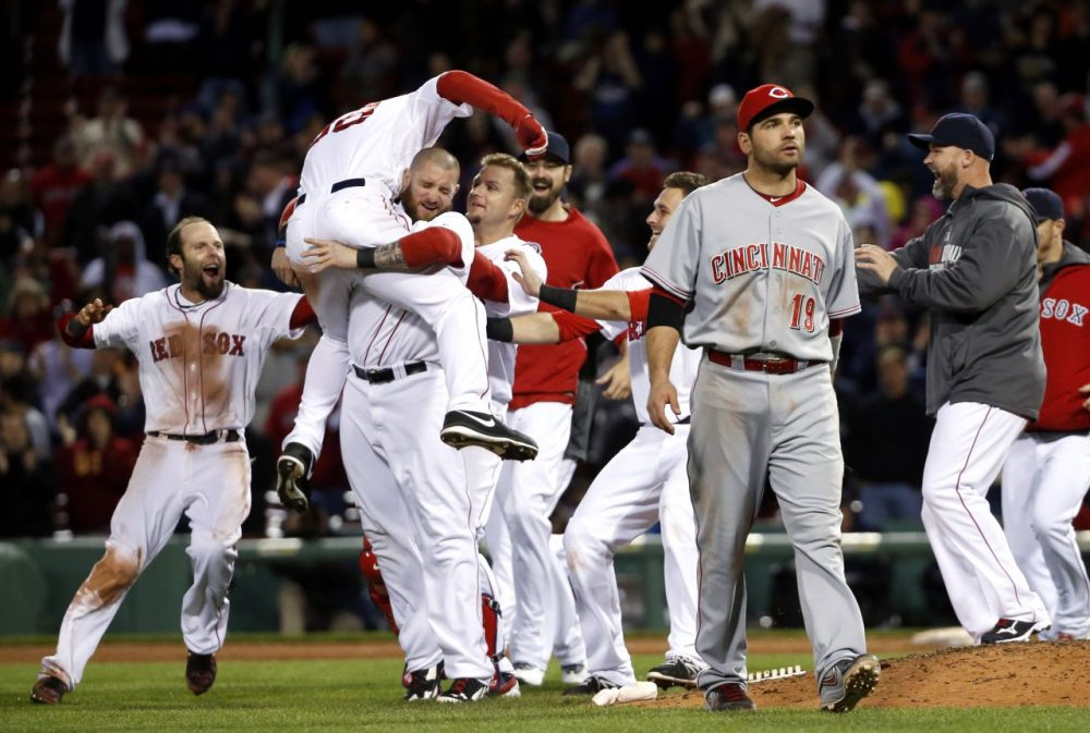 Boston Red Sox center fielder Grady Sizemore (38) jumps into the arms of teammate Jonny Gomes as he and teammates celebrate his walk-off single to defeat the Cincinnati Reds 4-3 in the 12th inning. (Elise Amendola/AP)