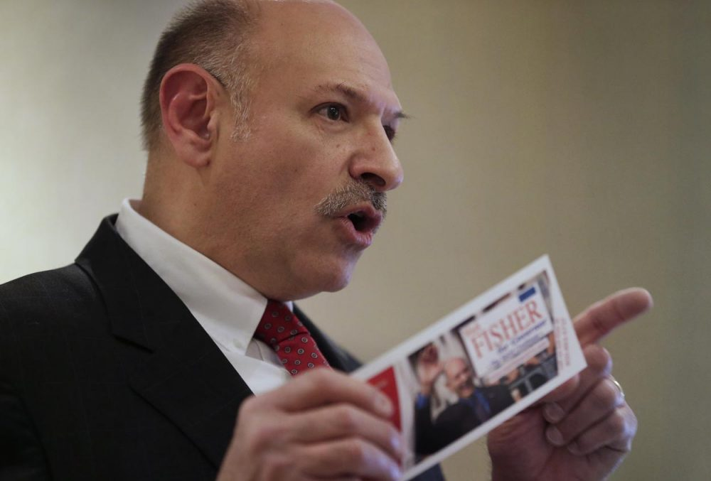 Republican candidate for governor of Massachusetts Mark Fisher displays a campaign brochure while facing reporters during a news conference Thursday. (Steven Senne/AP)