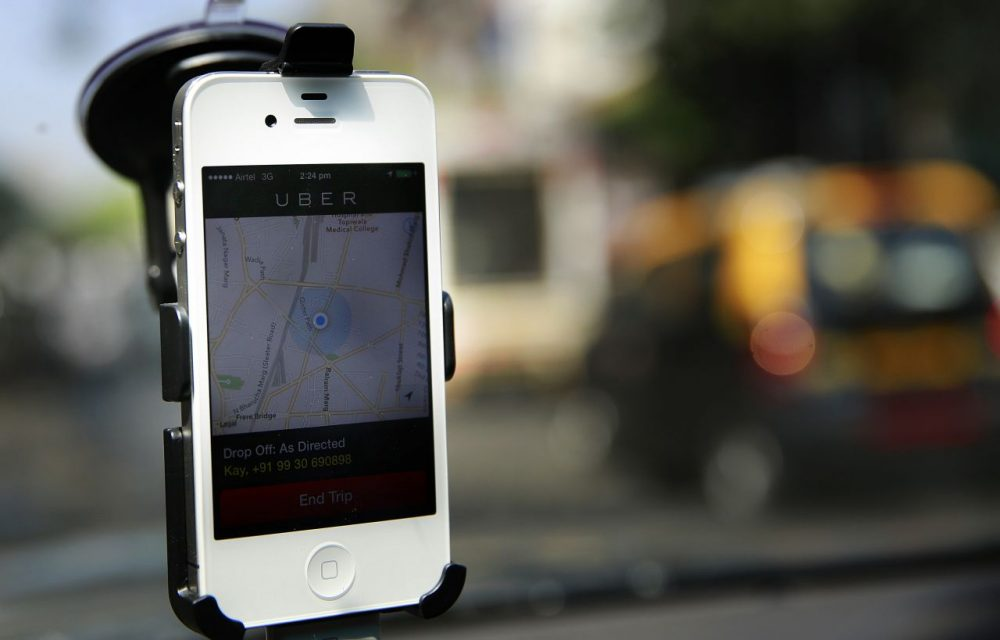 A smartphone is mounted on the glass of an Uber car. (Rafiq Maqbool/AP)