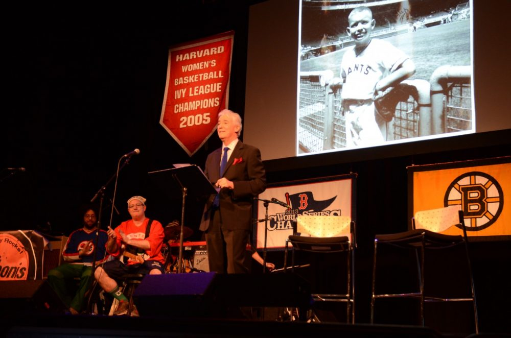 Scott Simon takes the stage at the Somerville Theatre with Bill's photo in the background. (Robin Lubbock/WBUR)