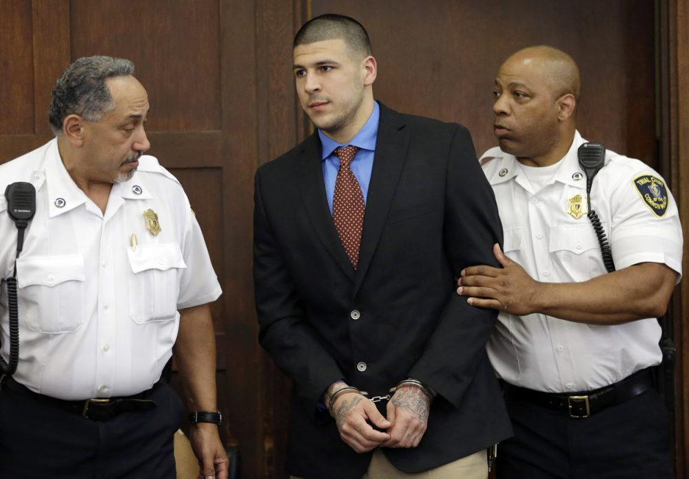 Former New England Patriots football player Aaron is escorted by court officers as he enters Suffolk Superior Court before a hearing on June 24 in Boston. Prosecutors allege that Hernandez ambushed and shot to death two men, Daniel de Abreu and Safiro Furtado, in 2012 after a chance encounter inside a Boston nightclub. Hernandez has pleaded not guilty. (Steven Senne/AP Photo)