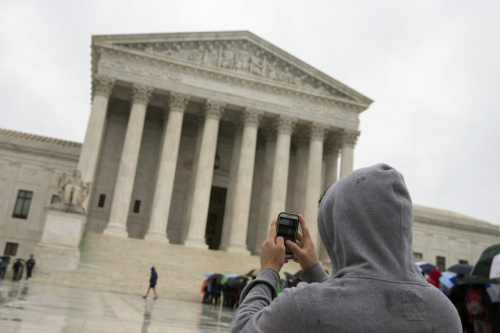 This April 29, 2014 file photo shows a Supreme Court visitor using his cellphone to take a photo of the court in Washington. A unanimous Supreme Court says police may not generally search the cellphones of people they arrest without first getting search warrants. The justices say cellphones are powerful devices unlike anything else police may find on someone they arrest. (AP)