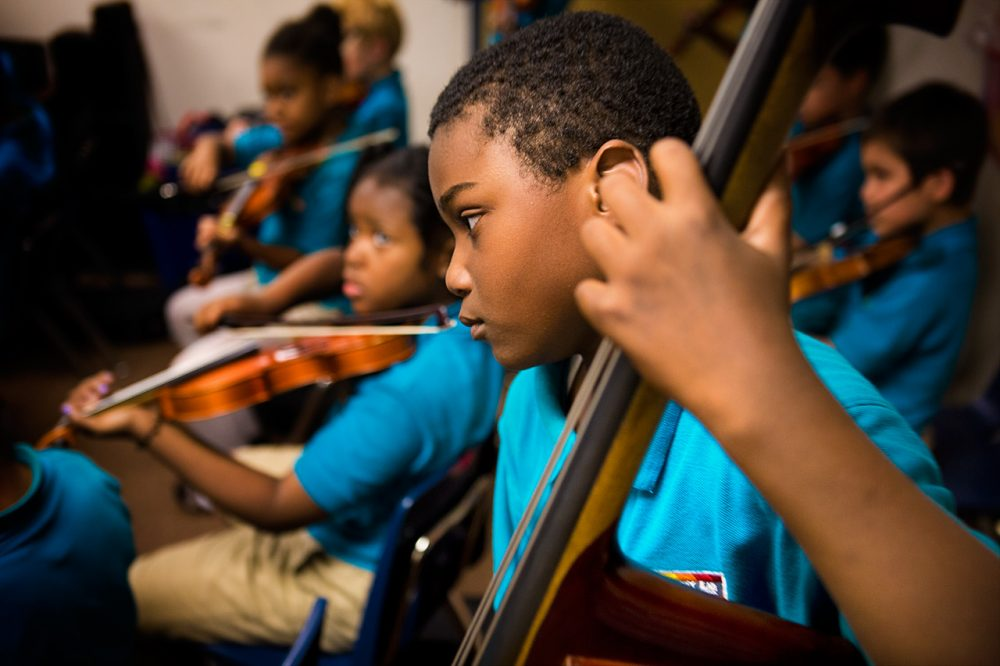 A bassist at the Conservatory Lab Charter School in Boston plays during a recital rehearsal. Research has found music instruction has beneficial effects on young brains. (Jesse Costa/WBUR)