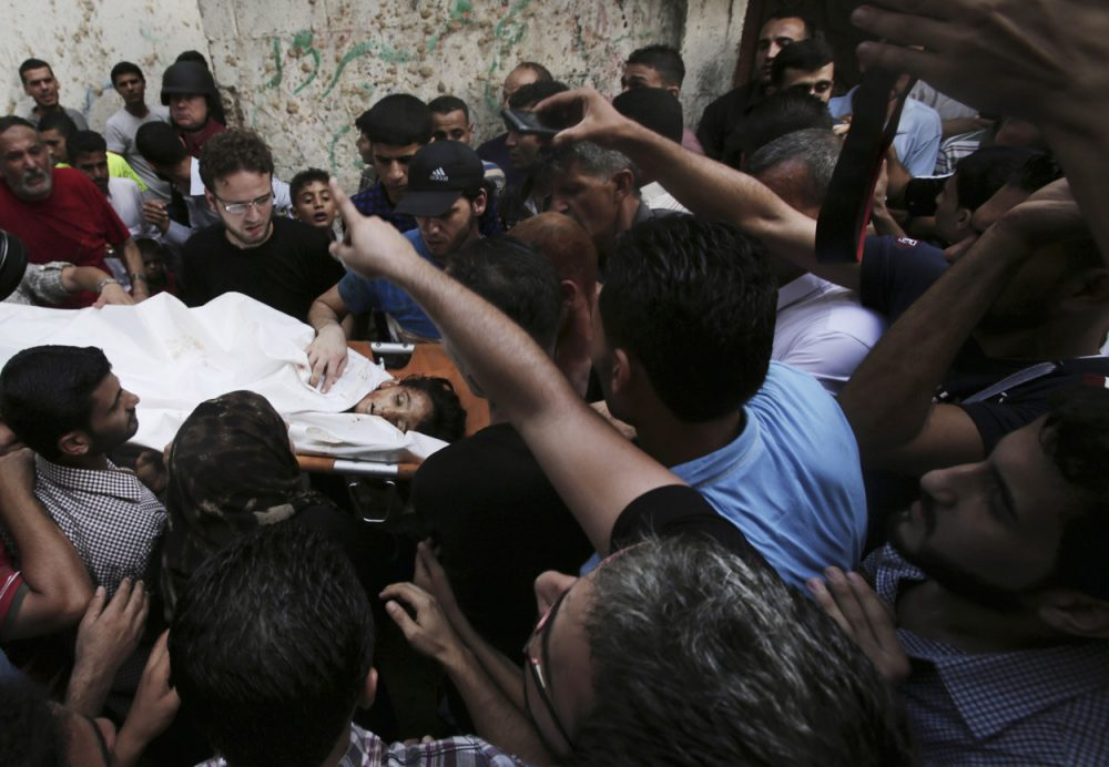 Palestinians carry the body of Gamal Ielian, 10, who was killed along with 9 other people, all but one of them children, in an explosion at a park at the Shati refugee camp in the northern Gaza Strip Monday. (Adel Hana/AP)