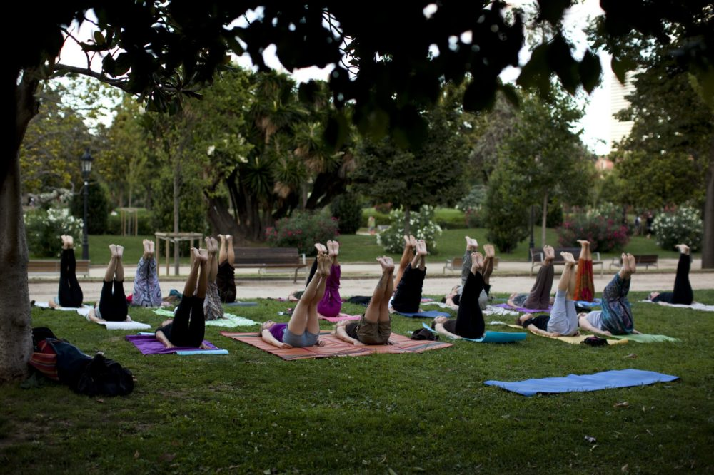 Men and women take part in an exercise class in a public park. (Emilio Morenatti/AP)
