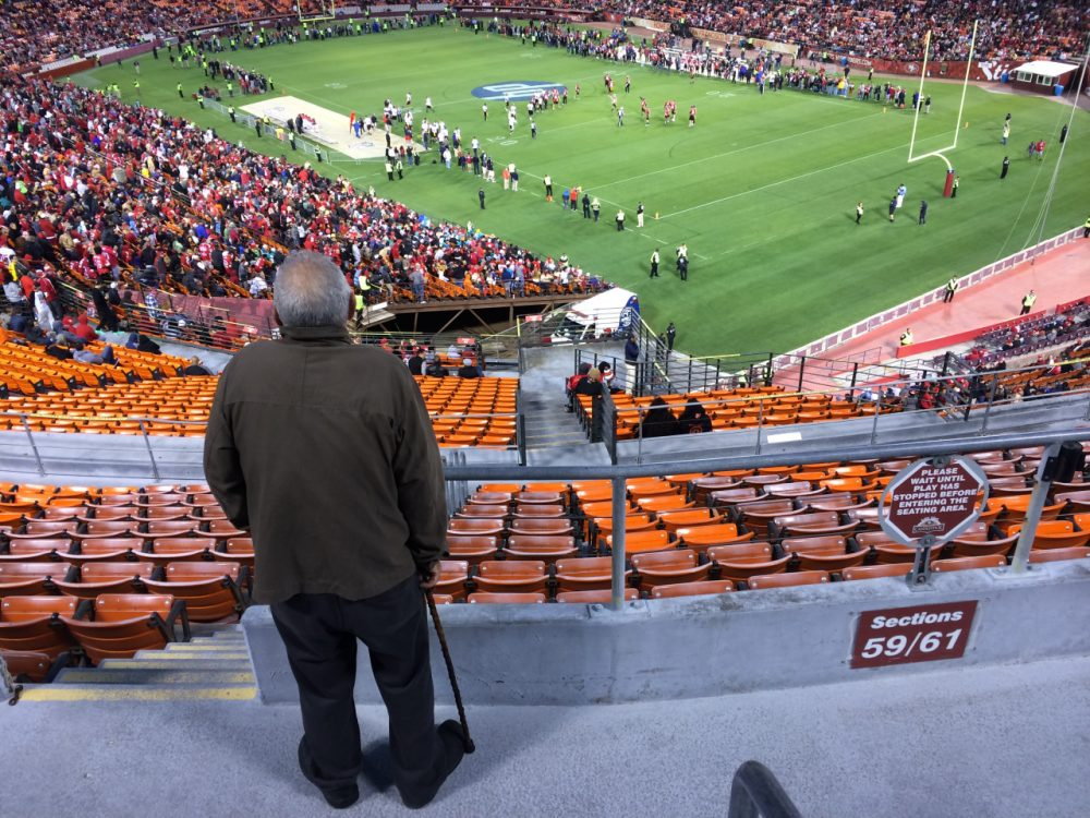"49ers fan John Barberini takes in second-half action during last week's ""Legends of Candlestick"" flag football game. (Dan Brekke)"