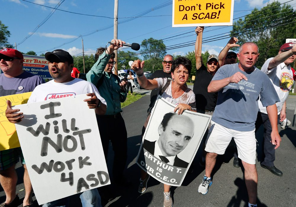 Protesters hold signs and taunt a car leaving the site of a Market Basket job fair in Andover on Wednesday. (Elise Amendola/AP)