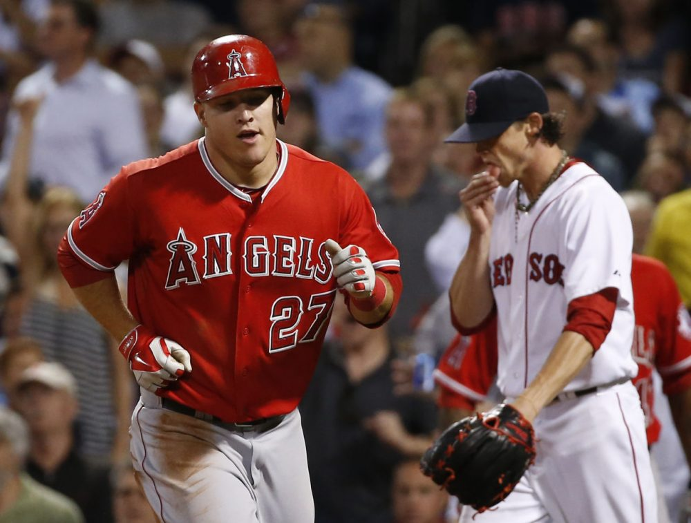 Angels' Mike Trout trots to the dugout after scoring on Josh Hamilton's sacrifice fly as Boston Red Sox starting pitcher Clay Buchholz, right, walks back to the mound. (AP/Elise Amendola)