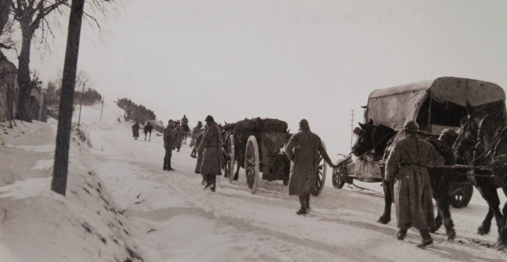Truck, soldiers and horse-drawn artillery walking on a snow-covered road. (Margaret Hall/Courtesy of the Massachusetts Historical Society)