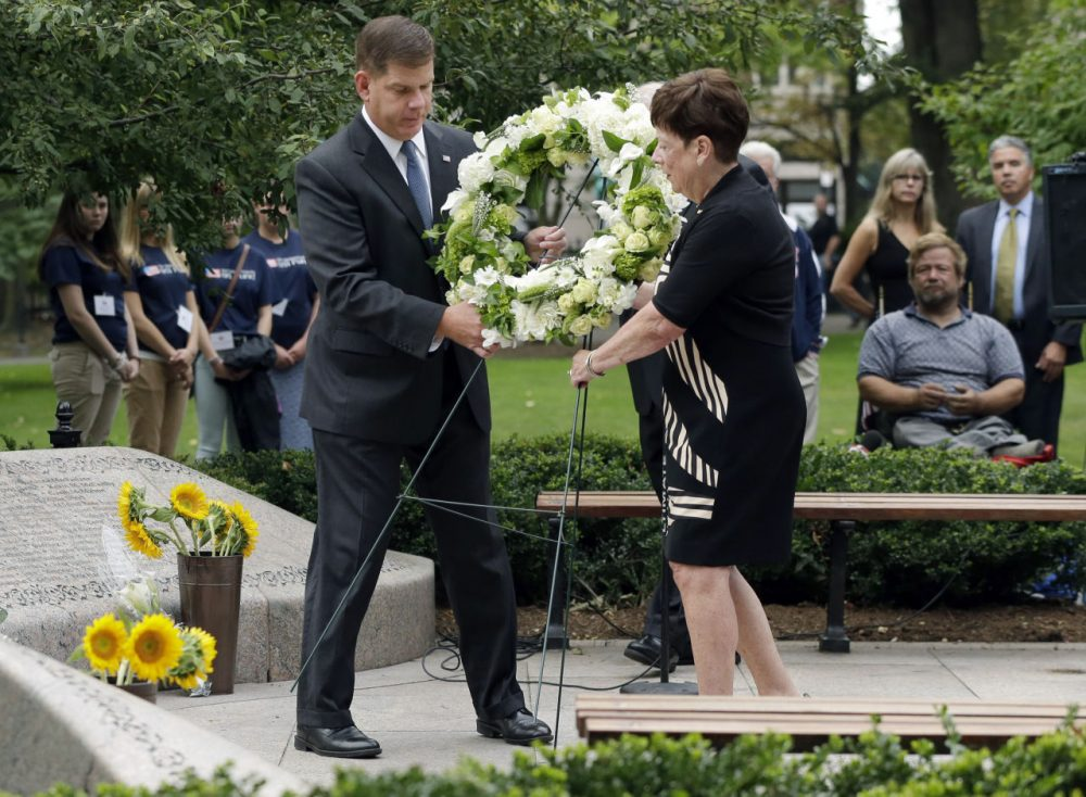 Boston Mayor Martin Walsh, left, and Maureen Gilligan place a wreath during a ceremony commemorating the anniversary of the 9/11 terrorist attacks at a memorial at the Public Garden in Boston. (Steven Senne/AP)