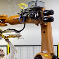 In this Jan. 15, 2013, photo, Rosser Pryor, Co-owner and President of Factory Automation Systems, examines a new high-performance industrial robot at the company's Atlanta facility.  (AP)
