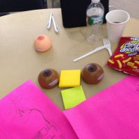 Detritus at hackathon's end includes junk food, coffee, diagrams and squeezable stress balls in the shape of breasts. (Carey Goldberg/WBUR)