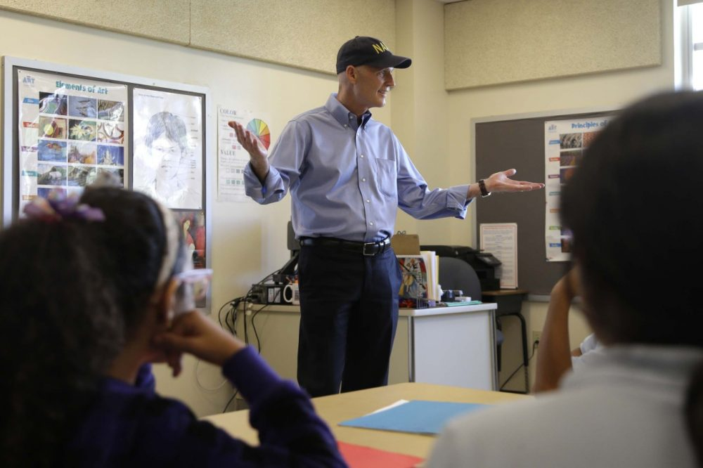 Republican Florida Gov. Rick Scott talks with students before holding a news conference with Alberto Carvalho, superintendent of Miami-Dade County Public Schools, at Southside Elementary School, Wednesday, Aug. 27, 2014, in Miami. (AP)