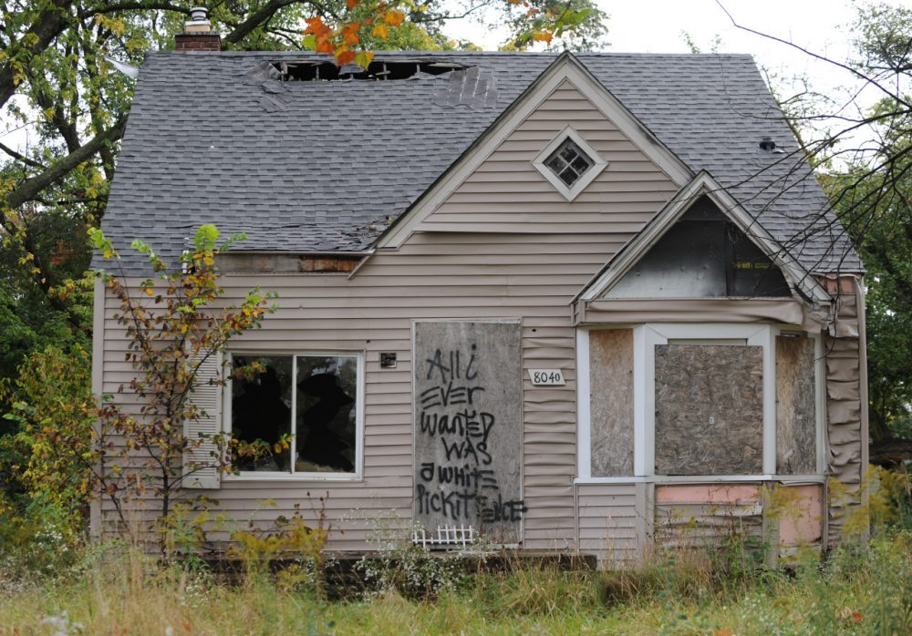"An abandoned home seen September 30, 2013 in Detroit, Michigan, is decorated with a piece of fencing and graffiti which declares ""All I ever wanted was a white picket fence."" (Mira Oberman/AFP/Getty Images)"