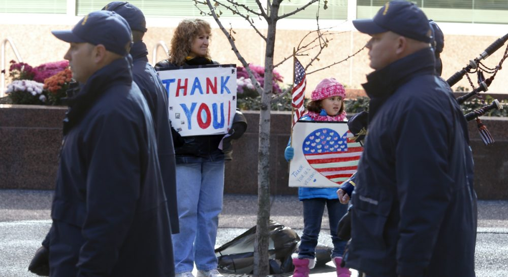 Linda J. Bilmes: Despite much effort, money and goodwill, the U.S. has no serious strategy for tackling the full range of challenges that veterans and their families are facing. Pictured: Sue Lippert, center left, and her granddaughter, hold signs thanking veterans as members of the U.S. Coast Guard march by in the Pittsburgh Veterans Day parade on Saturday, Nov. 8, 2014, in Pittsburgh. (Keith Srakocic/AP)