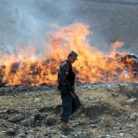 An Afghan police soldier walks past opium and narcotics set on fire during a drug burning ceremony on the outskirts of Kabul, Afghanistan, Wednesday, Oct. 29, 2014. (AP)