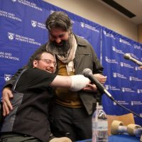 Arm transplant recipient Will Lautzenheiser uses his new arms to hug his partner, Angel Gonzalez, at a Brigham and Women's Hospital press conference. (Photo courtesy BWH)