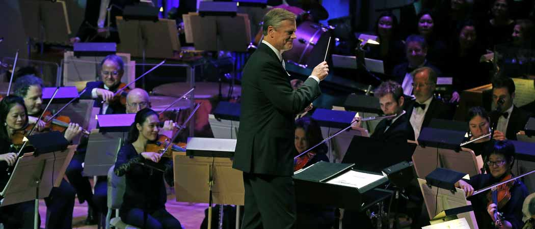 "Charlie Baker, waves a baton as the Boston Pops Orchestra performs ""Sleigh Ride"" during the 31st annual ""A Company Christmas at Pops"" at Symphony Hall. (Elise Amendola/AP)"