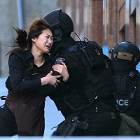 A hostage runs to armed tactical response police officers for safety after she escaped from a cafe under siege at Martin Place.  (Rob Griffith/AP)