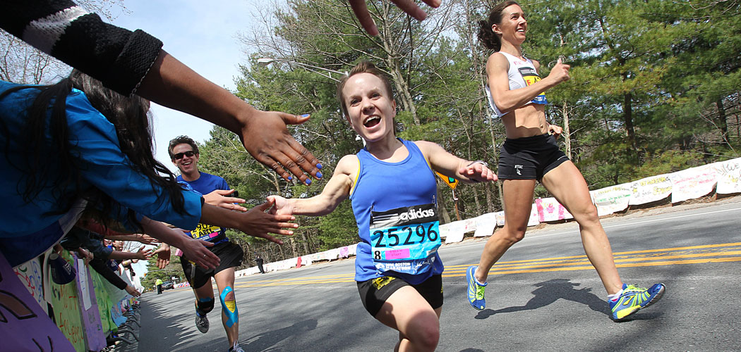 Juli Windsor, foreground, 27, returned to the Boston Marathon in 2014 after being stopped less than a mile shy of the finish after two bombs exploded at last year's race. Reporter and documentarian David Abel is running to the left. (Courtesy of Suzanne Kreiter/The Boston Globe)