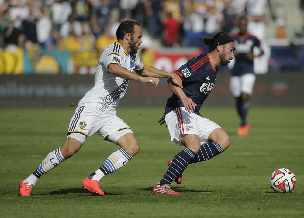 Los Angeles Galaxy's Landon Donovan, left, grabs the arm of New England Revolution's Lee Nguyen during the first half of the MLS Cup championship soccer match Sunday. (Jae C. Hong/AP)