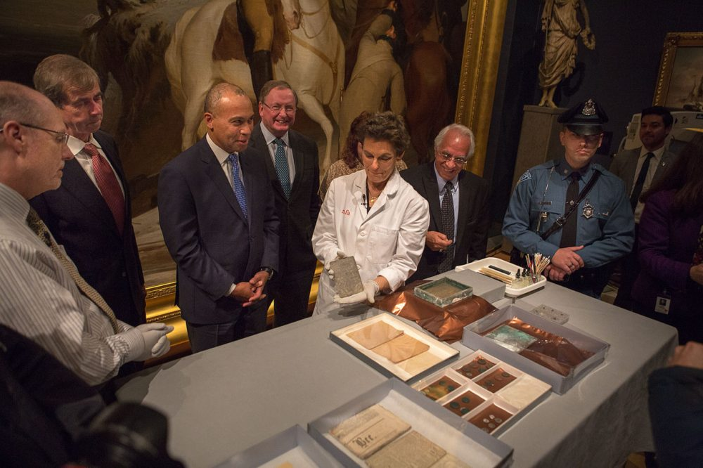 State and museum officials, including Gov. Deval Patrick and Secretary of State William Galvin, watch as Pam Hatchfield, the MFA's head of objects conservation, holds up a silver engraving found in the time capsule. (Jesse Costa/WBUR)