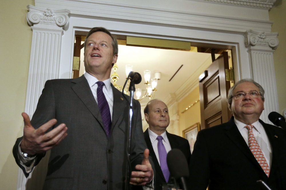 Gov. Charlie Baker speaks to reporters as Senate President Stanley Rosenberg, center, and House Speaker Robert DeLeo look on during a news conference Monday outside the governor's office. The trio are facing a state budget gap. (Steven Senne/AP)