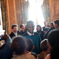 Lassana Bathily, center, talks with children prior to speeched from U.S. Secretary of State John Kerry and Paris' mayor Anne Hidalgo, at the Paris' city hall, Friday, Jan. 16, 2015. The government announced Thursday it would give citizenship to a Malian immigrant who saved several Jewish shoppers last week by hiding them in the kosher market's basement before sneaking out to brief police on Coulibaly, the hostage-taker upstairs. (AP)