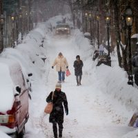 A plow rolls down the street as people trudge on foot down Joy Street on Beacon Hill Monday. (Jesse Costa/WBUR)